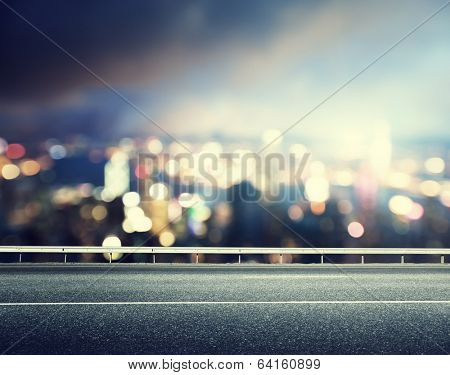 Asphalt road and blurred modern city
