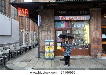 BOLOGNA, ITALY - APRIL 19, 2014: A woman stands outside a store selling tobacco products in Bologna, Italy, on Saturday, April 19, 2014.