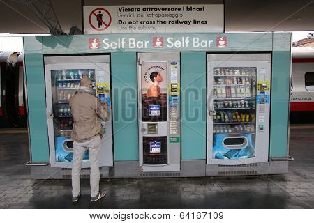 BOLOGNA, ITALY - APRIL 19, 2014: A man buys a snack from an outdoor vending machine in Bologna, Italy, on Saturday, April 19, 2014.