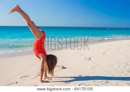Beautiful gymnastic little girl on beach