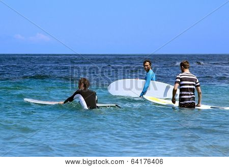 Surfers In Ocean With Surf Boards