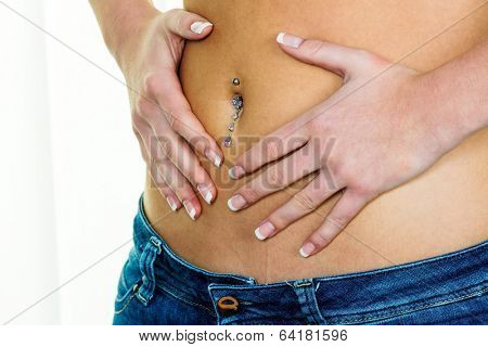 a woman has abdominal pain or stomach pain. hands in a heart shape around navel piercing.