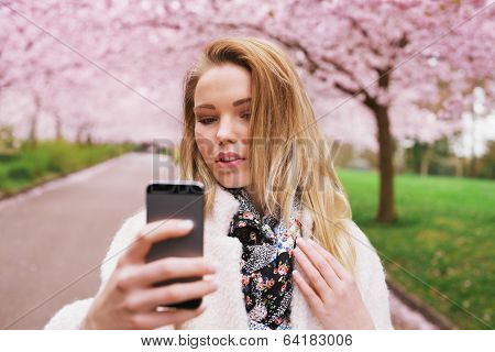 Attractive Woman Photographing Herself At The Spring Garden
