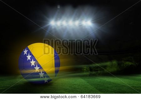 Football in bosnia and herzegovina colours against football pitch under spotlights