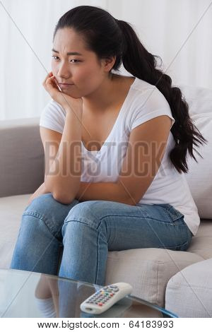 Bored woman sitting on couch at home in the living room