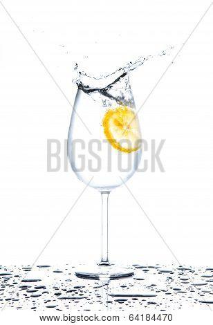 Lemon Splashing Into Glass Of Water On White Background