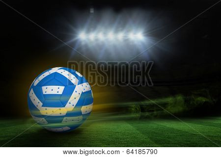 Football in honduran colours against football pitch under spotlights