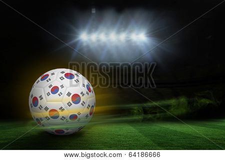Football in south korea colours against football pitch under spotlights