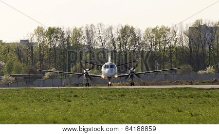 White turboprop aircraft on the runway, front view