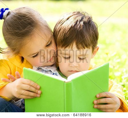 Little Boy And Girl Is Reading Book