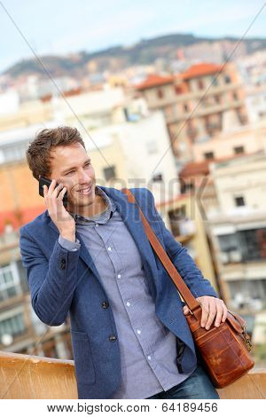 Man on smart phone - young business man talking on smartphone. Casual urban professional businessman using mobile cell phone smiling happy walking. Handsome man wearing suit jacket in Barcelona, Spain