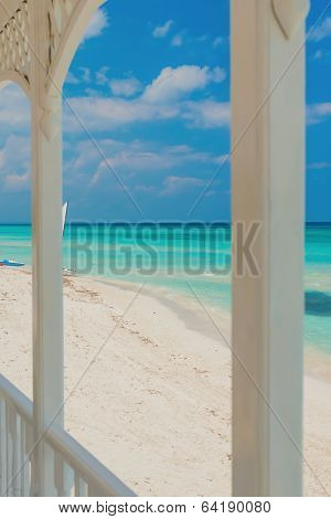 View of Varadero beach in Cuba framed by the columns of a beautiful wooden terrace (focused on the beach)