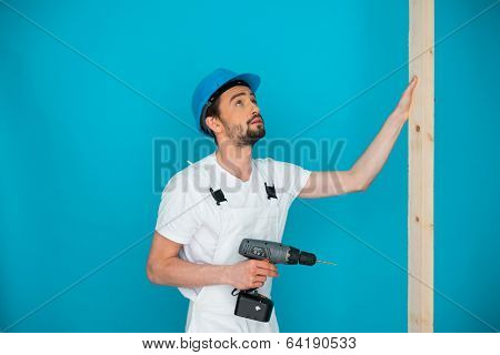 Workman in a hardhat holding a battery-operated hand drill and a plank of wood as he does carpentry on a construction site or during home renovations, on a blue wall