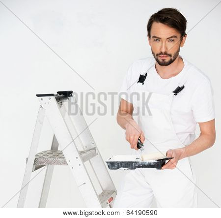 Painter standing on a stepladder holding a paint roller in his hand as he surveys a white wall, with copyspace