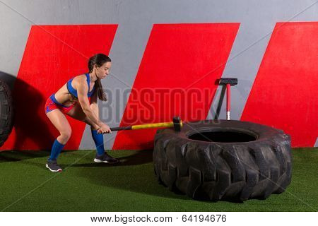 Sledgehammer Tire Hits woman workout at gym with hammer and tractor tire