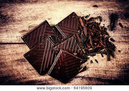 Chopped Chocolate Bar On Wooden Background Closeup. Broken Dark Chocolate Bar On Wood Table Macro.