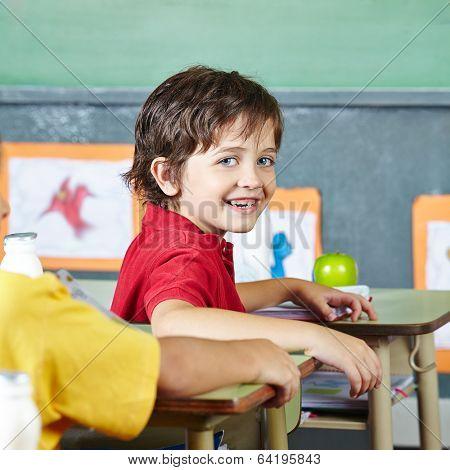 Happy abecedarian child sitting smiling in elementary school classroom