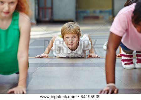 Children doing push ups in PE in elementary school
