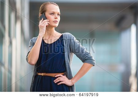 Portrait of a sleek young woman calling on a smartphone in an urban/city context (shallow DOF; color toned image)