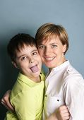 foto of tease  - Naughty boy of seven showing his tongue teasing while his mother posing for a shot in studio. Concept of misbehavior. ** Note: Soft Focus at 100%, best at smaller sizes - JPG