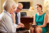 picture of 50s 60s  - Older Couple Talking To Counsellor Using Digital Tablet - JPG
