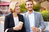 stock photo of takeaway  - Business Couple Walking Through Park With Takeaway Coffee - JPG
