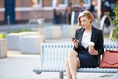 stock photo of sitting a bench  - Businesswoman On Park Bench With Coffee Using Mobile Phone - JPG