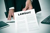 stock photo of lawyer  - a lawyer in his office showing a document with the text lawsuit written in it - JPG
