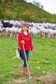 picture of shepherdess  - Kid girl shepherdess happy with flock of sheep and wooden stick in Spain - JPG