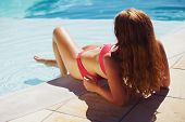 stock photo of sunbather  - Pretty young lady lying by swimming pool and enjoying a sunbath - JPG