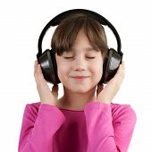 stock photo of have sweet dreams  - Happy little girl having fun listening to music on headphones - JPG