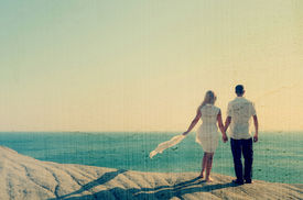 foto of sympathy  - Loving couple looking at the sea holding hands - JPG