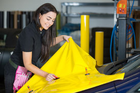 picture of bubble sheet  - Car wrapping specialists straightening vinyl foil or film to remove ari bubbles - JPG