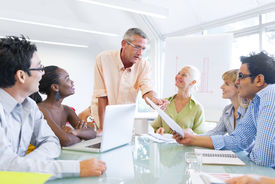 stock photo of professor  - Group of Business People Learning With the Help of Their Mentor - JPG