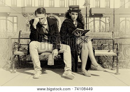 Young Couple In Quarrel Sitting On Bench In Old Town