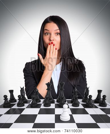 Surprised businesswoman looking at camera with Chessboard