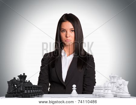 Upset businesswoman looking at camera with chess board