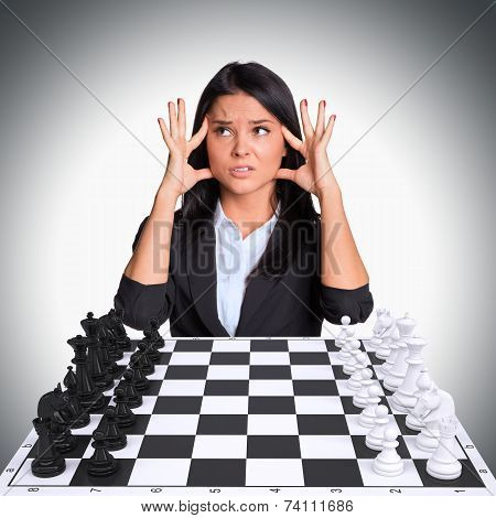 Lost in thought woman looking up with Chess board