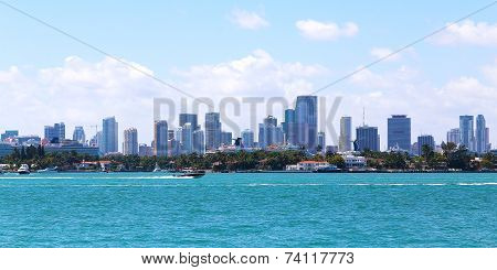 A view on Miami city skyline with cruising motoboats.