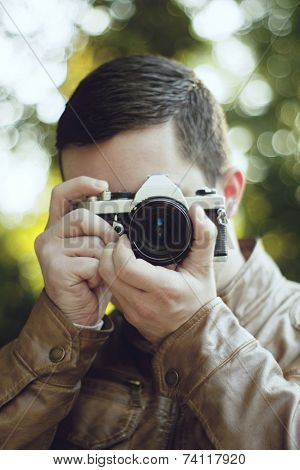 Young male photographer aiming for a shot with with beautiful vintage camera