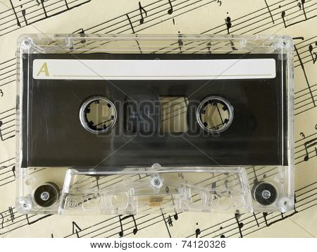 Cassette on old sheet music, closeup
