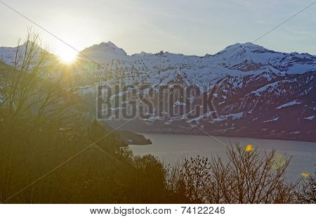 Flaring Sun Rising Behind Eiger Peak In Jungfrau Region Of Switzerland Near Thuner-see