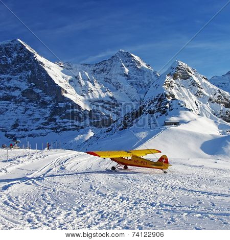 Yellow Airplane At The Swiss Winter Mountain Ski Resort