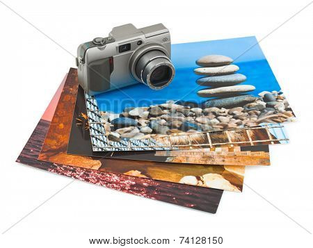 Camera and photo printouts isolated on white background