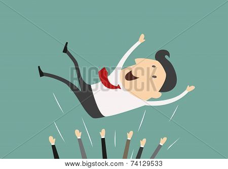 Successful businessman being thrown in the air