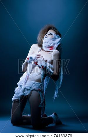 Studio snapshot of slim model posing as mummy