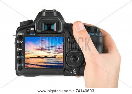 Hand with camera and beach landscape (my photo) isolated on white background
