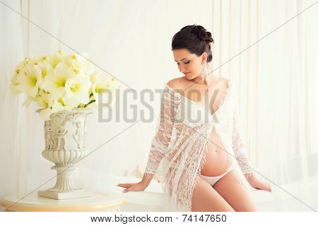 Gentle Pregnancy. Beautiful Pregnant In Light White Lace Negligee In The Bathroom