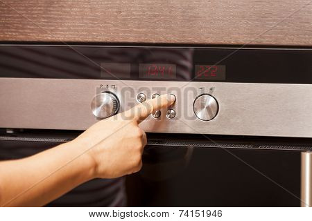 Close Up Of Hand Turning Knob On Oven