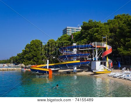 Waterslide and catamaran on beach - vacations background